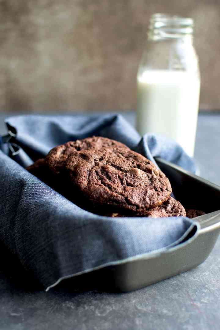 kitchen towel lined baking pan with chocolate drop cookies