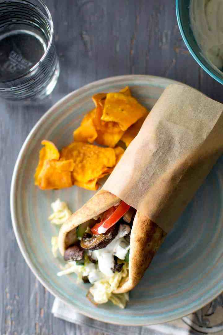 Bluish grey plate with Pita sandwich filled with tomatoes, cucumber and mushroom