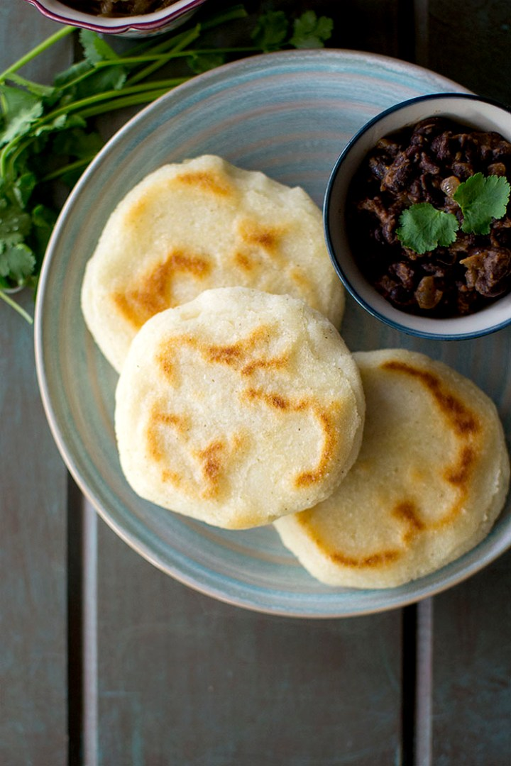 Blue plate with 3 arepa and black bean filling