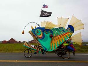 An art bike of a green, blue, and oranage monster fish complete with pirate flag and teeth.