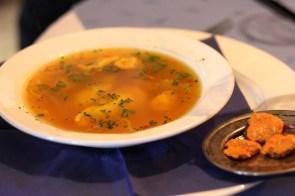 Suppe aus regionalen Edelfischen mit Saiblingsravioli und Safran, dazu Brotchips und Tomaten-Chili-Paste