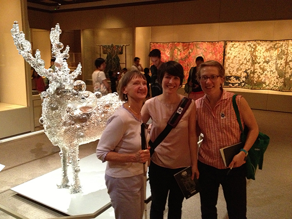 Linda, Rachel and Katie smiling inside a contemporary Asian art gallery at the Met museum. There is a very unusual sculpture in the background of a real deer, taxidermied and covered in glass orbs of variable sizes, as if it had been dunked in an oversized glass of club soda, and all the bubbles were sticking to its sides.
