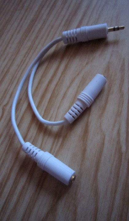 A white cable with one 3.5mm male audio jack plug connected to two 3.5mm female jacks.