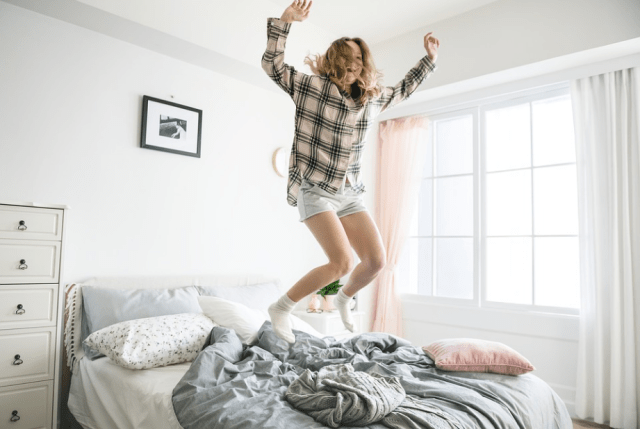 a woman jumping on the bed