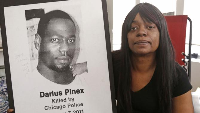 """Gloria Pinex holds a photo of her son Darius Pinex, Thursday, Dec. 17, 2015, photo at her home in Chicago. Darius, was killed by Chicago police in 2011. After the recently released video of a Chicago officer firing 16 bullets into the body of Laquan McDonald, Pinex said, """"That video showed what we are going through out here, what these police officers are covering up."""" (AP Photo/M. Spencer Green)"""