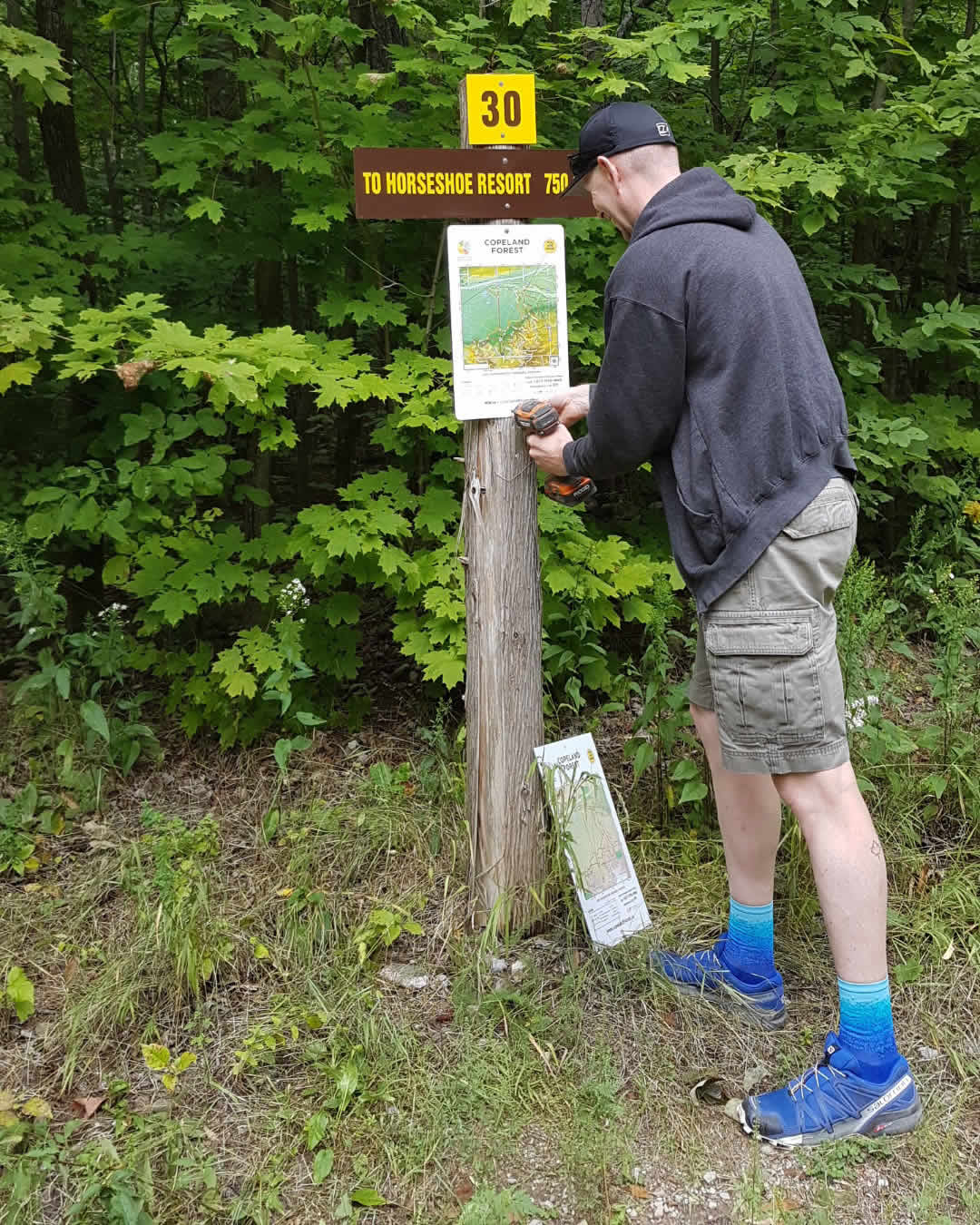 a volunteers replaces a trail map in the copeland forest