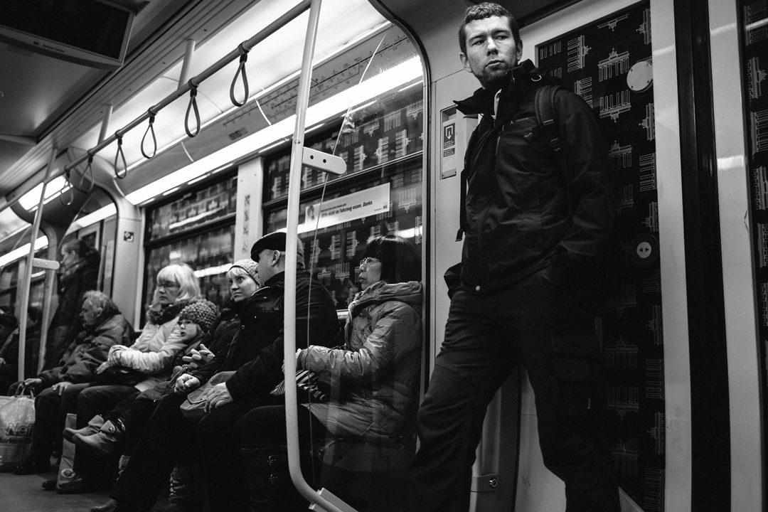 a group of people sitting on the subway, a man stands by the door