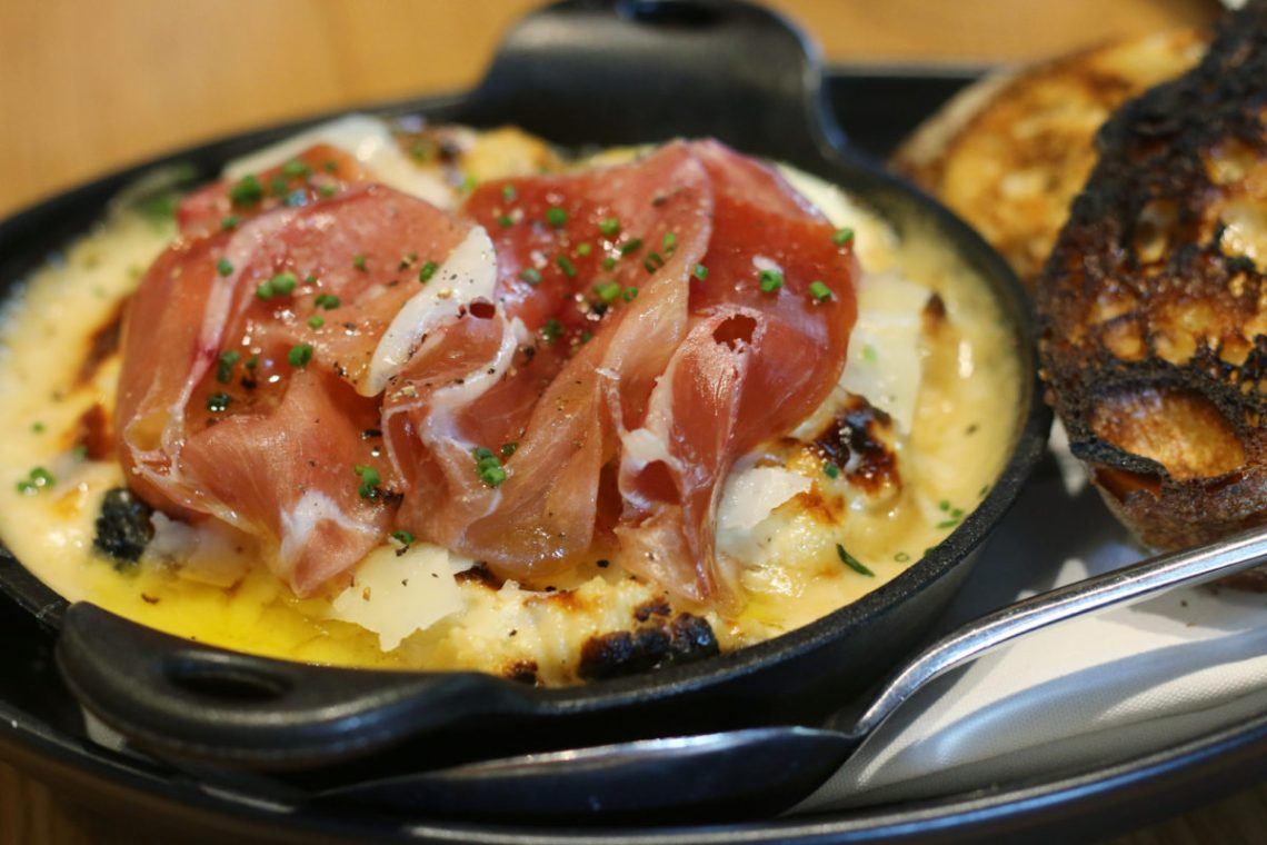 Wood oven baked eggs topped with prosciutto Bacon, sunny side up eggs and cheddar breakfast sandwich from restaurant Glass & Vine in the Grove. It's AMAZING! Click to read more or pin and save for later! Coral Gables | Miami | Coconut Grove | Florida