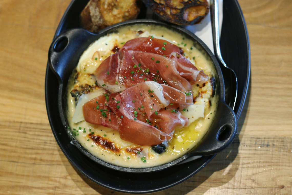 Wood oven baked eggs topped with prosciutto from restaurant Glass & Vine in the Grove. It's AMAZING! Click to read more or pin and save for later! Coral Gables | Miami | Coconut Grove | Florida