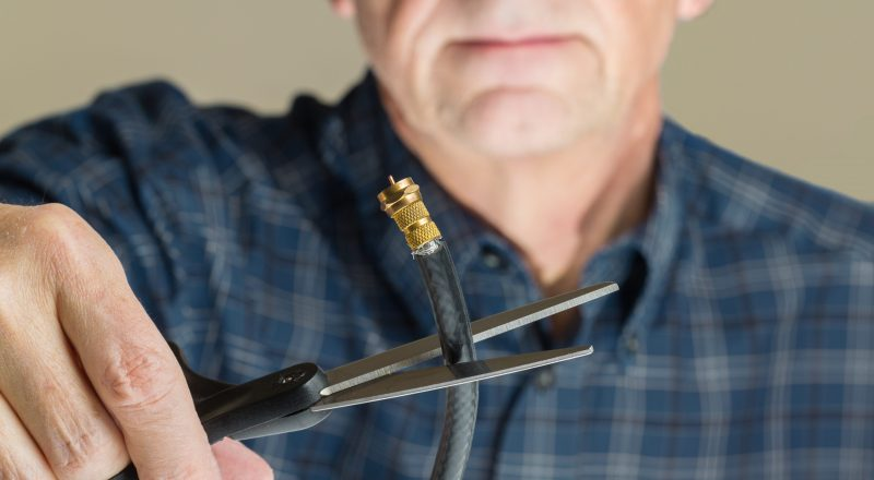 Cutting the cable connection to coax connector illustrating retired people cancelling cable TV service