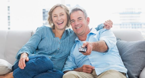 Cheerful couple cuddling and sitting on the couch watching tv at home in the living room