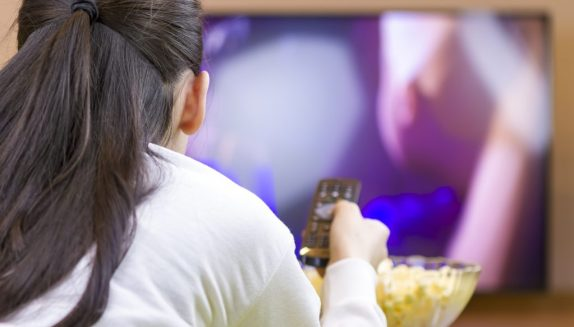 Teenager girl with remote control laying down and watching tv eating popcorn.