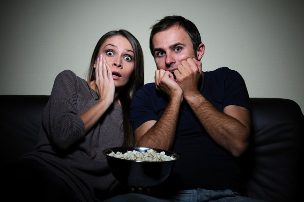 Young couple sitting on a sofa watching scary movie on tv