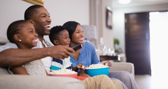Cheerful family having popcorn while watching television at home