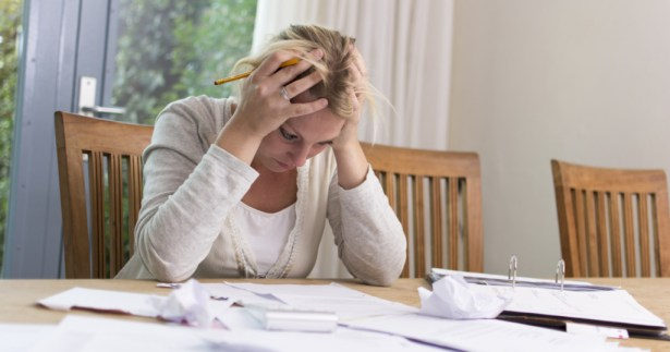 woman at table frustrated with bills