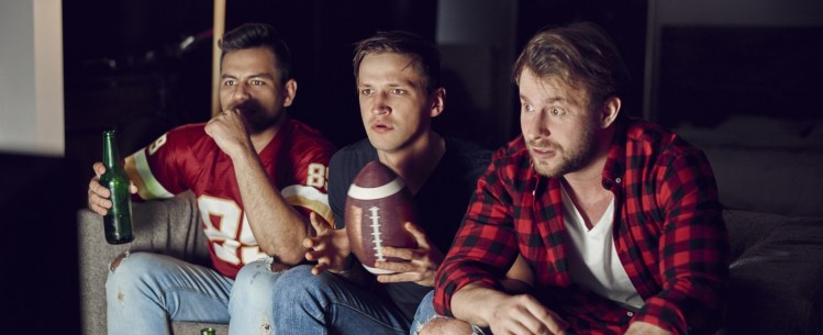 3 men sitting on couch watching tv