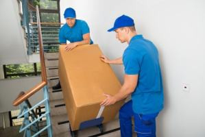 Men Moving Box Down Stairs