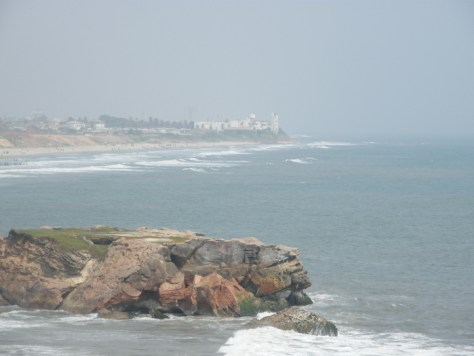 Looking at ocean, a rock formation lookout, then ocean and the cityscape in the distance