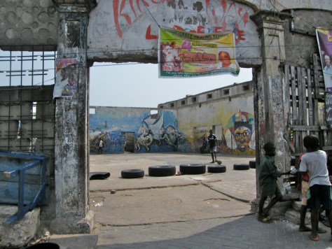 """Large square entranceway with a colourful poster that says, """"Divine Grace Healing Temple, come to Jesus and be healed"""" and art painted on the interior walls"""