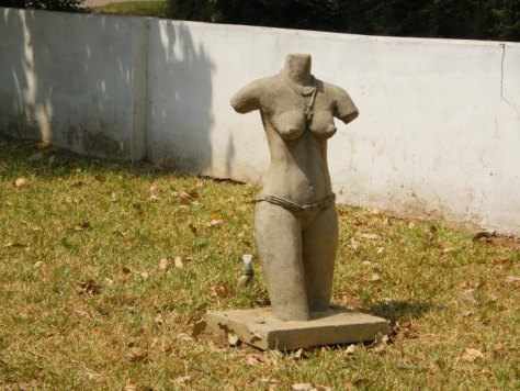 The headless, armless trunk of a woman's body wearing a cross pendant around her neck and a bikini-type bottom