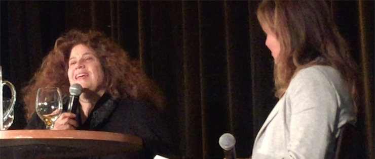 Poet Laureate of Toronto Anne Michaels with CBC's Gill Deacon sit at a table on stage with mics in their hands