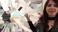 Blaszczak stands in front of her painting, a bold multifaceted piece on canvas, gesturing with her right hand.