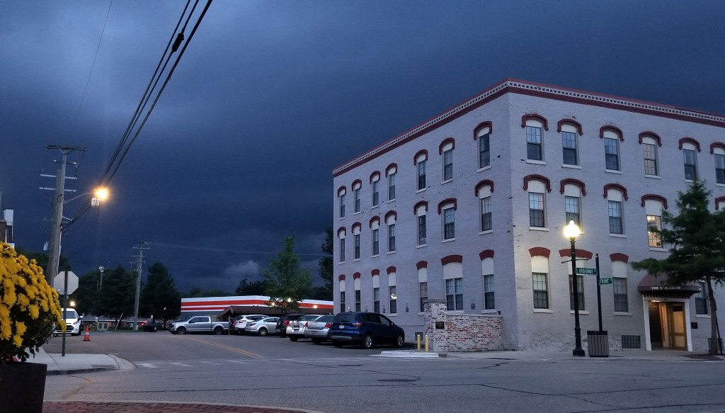 Dark clouds from thunderstorm over town building