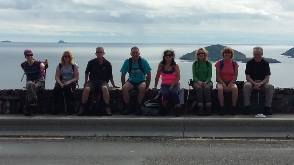 About Us - Backpackers taking a break from hillwalking on the wall at Coomakista Pass near Waterville, Co. Kerry