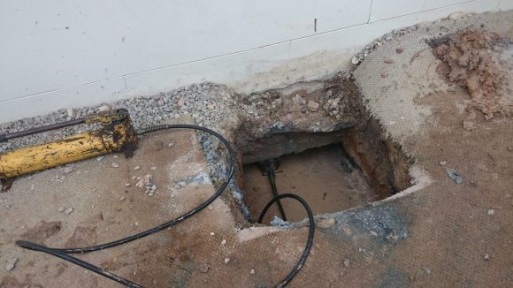 As a part of house underpinning, hydraulic jacks are used to lift a house back into place.