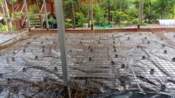Picture of a concrete house slab before it is poured. The black sheet under the mesh is a vapour barrier.