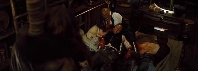 Marquis Warren en de sheriff kijken lachend naar de hangende Daisy Domergue