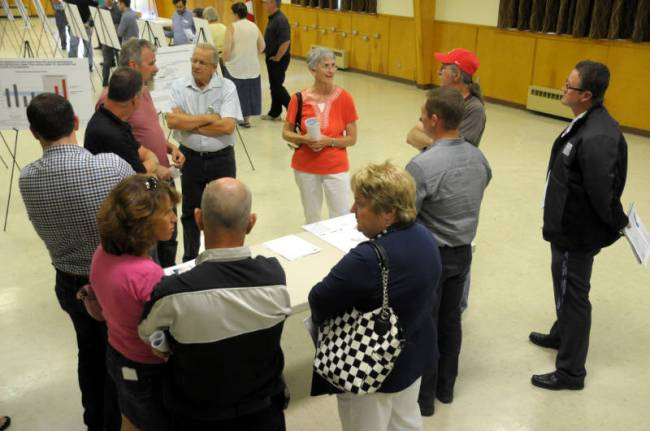South Dundas councillors and staff, spokesmen from EDP Renewables and local residents chat about the proposed South Branch Wind Farm II project during an open house Aug. 5, 2015 at Matilda Hall in Dixons Corners. (Cornwall Newswatch/Bill Kingston)