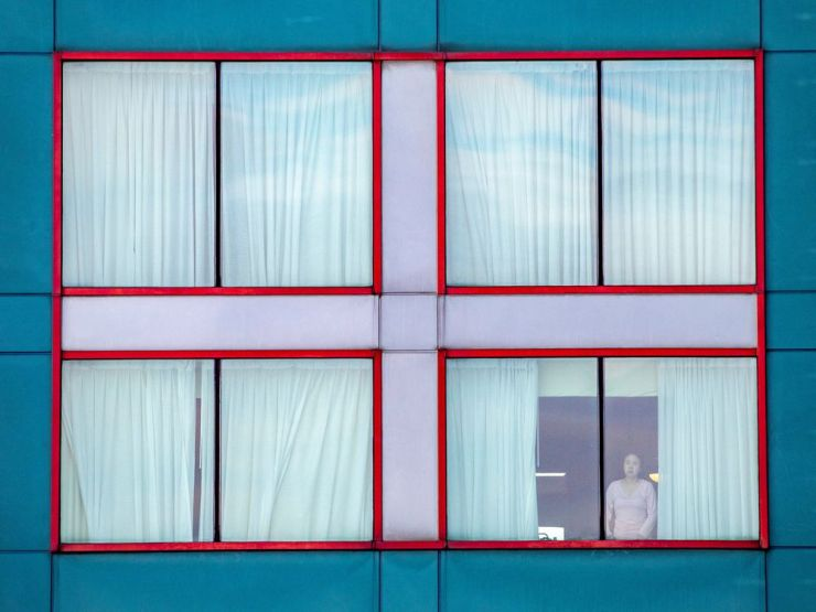 A person looks out the window of a quarantine hotel in Toronto.