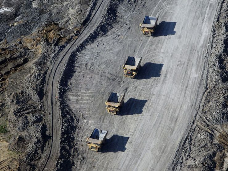 Dump trucks loaded with oilsands drive through a mine in this aerial photograph taken near Fort McMurray, Alberta.