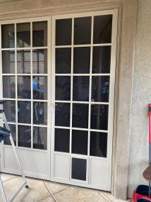 French door white Cape Cod doors with small pet door installed.