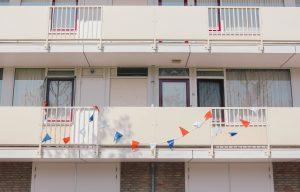 Eerste verdieping gallerij flat ramen deuren gordijnen dicht wit blauwe orangje vlaggetjes gedrapeerd over ballustradefoto door 'Omar Osman' (omarsolimanosman@gmail.com)