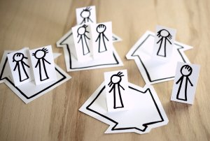 stickfigures drawn on paper and cut out standing in flat drawn houses seperate from each other