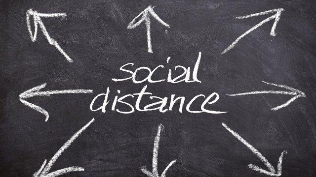 social distance geschreven op een krijtbord met pijlen eromheen die naar buiten wijzen