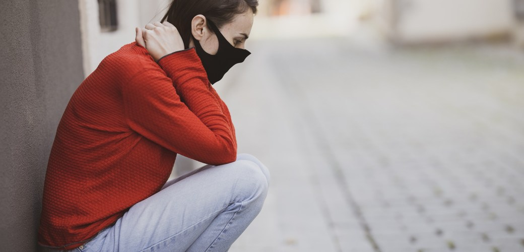 woman haunched down outside wearing a mask