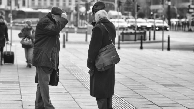 twee oudere mannen die hun hoed voor elkaar afnemen op een plein