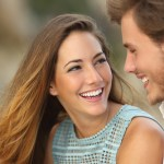 Funny couple laughing with a white perfect smile and looking each other outdoors with unfocused background, cfs magazine