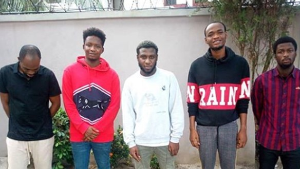 Suspected yahoo boys smile and pose with swag for the camera as EFCC charges them