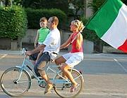 Una famiglia in bicicletta con il tricolore nelle strade di Firenze (Ansa)
