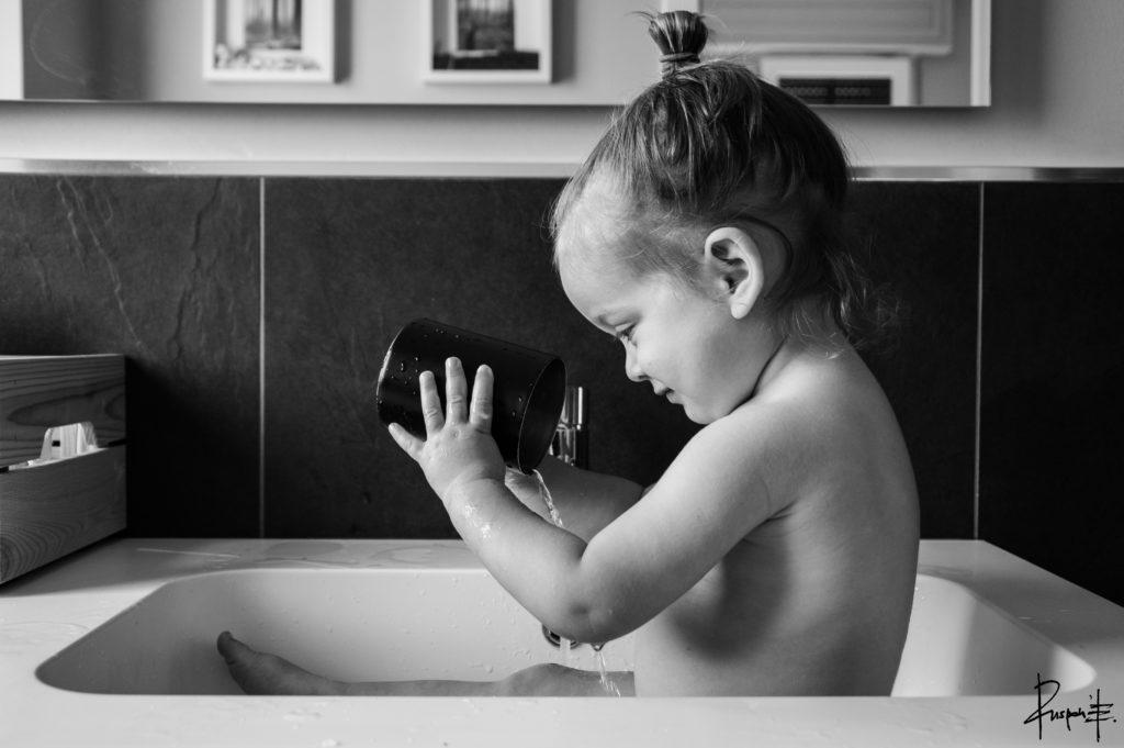 Bambina piccola fa un bagnetto e gioca con l'acqua nella vasca