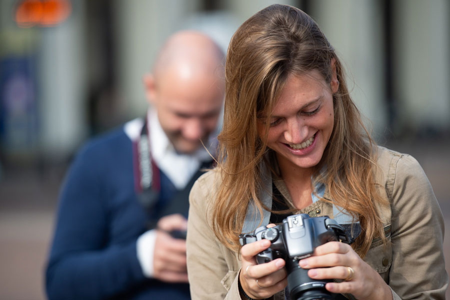 ragazza sorride guardando la sua macchina fotografica