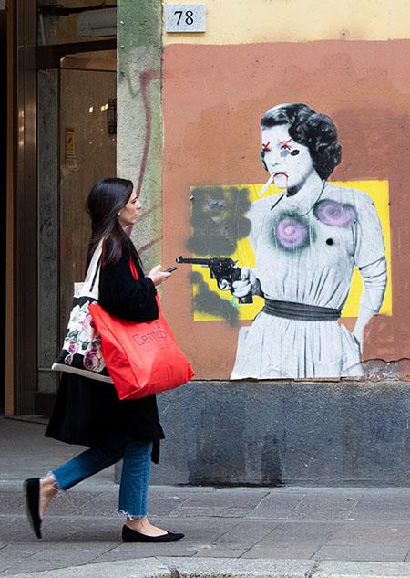 Donna cammina davanti ad un murales in bianco e nero