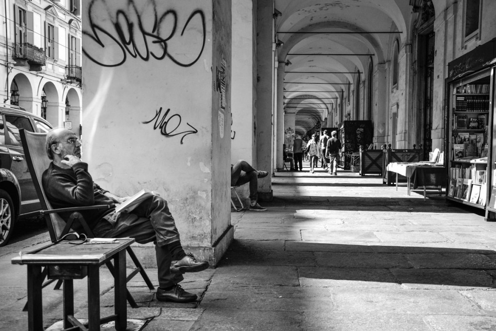 Negoziante seduto davanti alla bancherella sotto i portici di Via Po