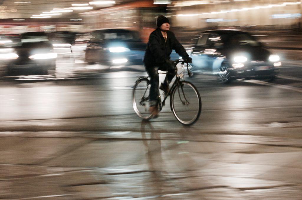 Ragazzo in bici in movimento nel traffico cittadino