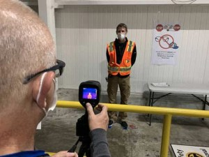 Todd Haylett, facilities manager, has his temperature measured by George Sylvester, manufacturing engineering manager, at the General Motors assembly plant in Spring Hill on May 11.