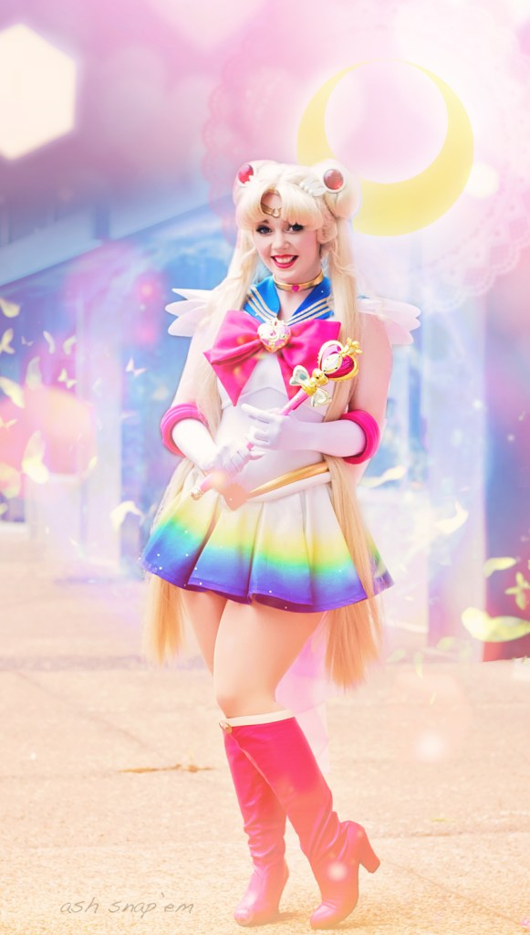 Cosplayer Dani poses as Super Sailor Moon, holding her Spiral Heart Moon rod and smiling at the camera.